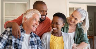 Two couples about the age of people making the change to Medicare gather together smiling.