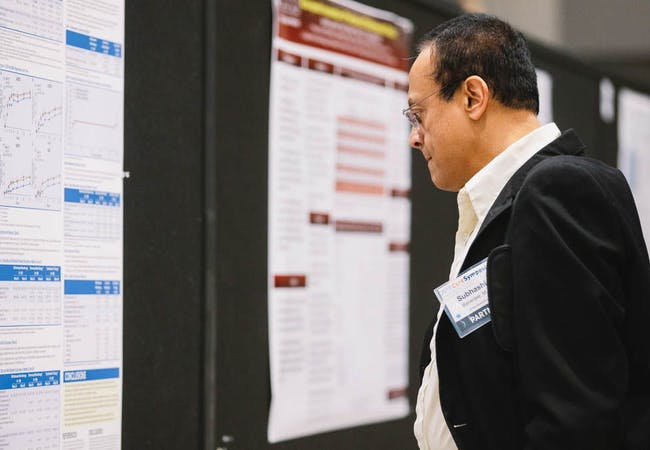 A male in a suit inspects a research poster at a training symposium.