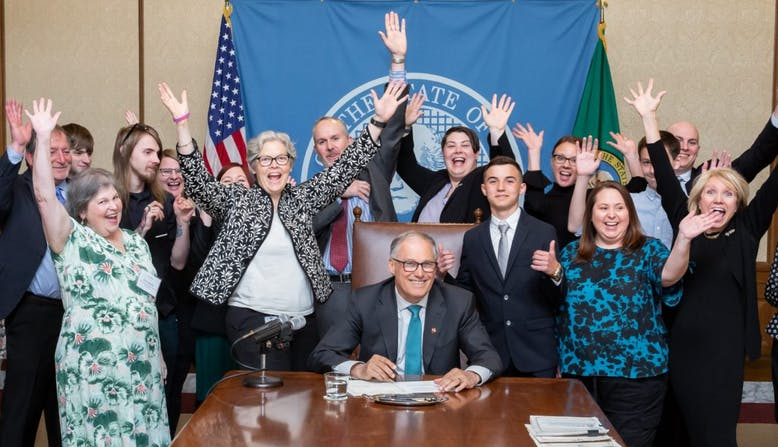 Group of people celebrating at a bill signing.