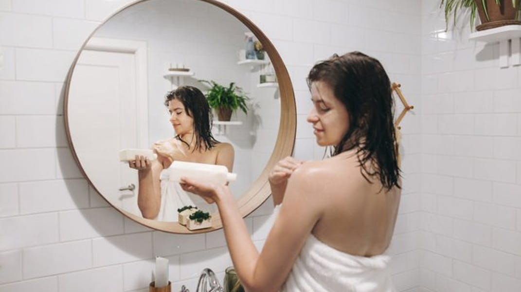 A woman in a towel holds a bottle and applies a cream to her shoulders in a bathroom.