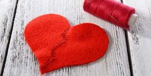 A felt heart mended in the middle with needle and thread.