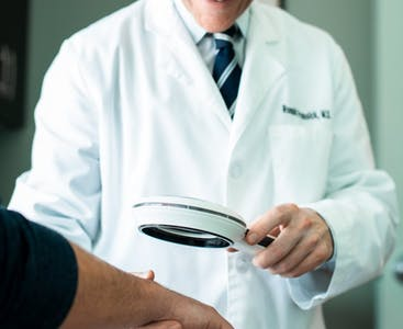 Dr. Prussick examines a patient's hands under a magnifying glass.