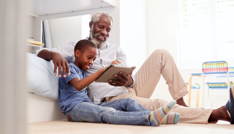 A grandfather sitting with his grandson in a bedroom using digital tablet together.