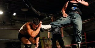 Michael Murray lands a kick on his opponent's head during a professional wrestling match.