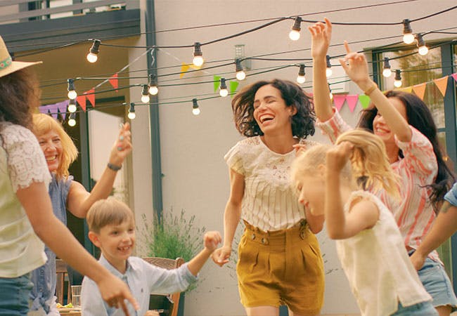 A dance party outside with kids and adults.