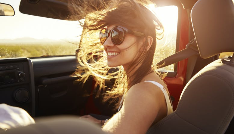 Young woman sits in the passenger seat of a car smiling.