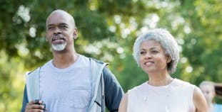 A man and a woman engage in a brisk walk outside.