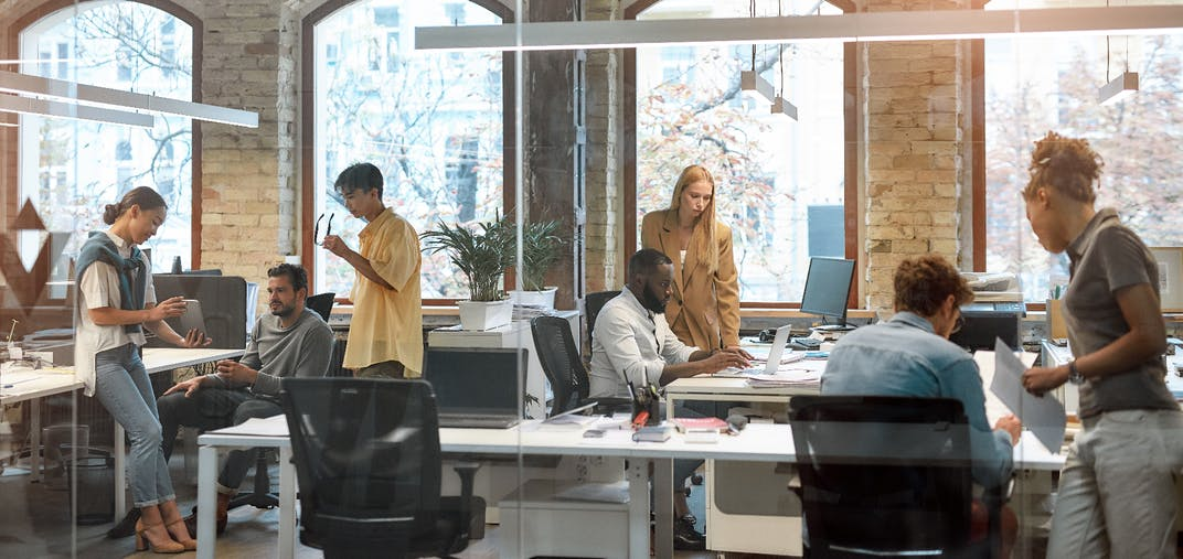 A woman and man discuss business in an open office setting.