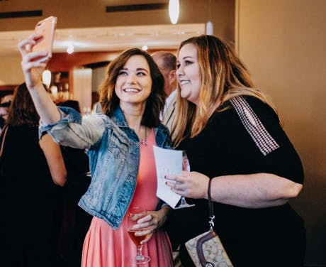 Two women pose for a selfie during an event.