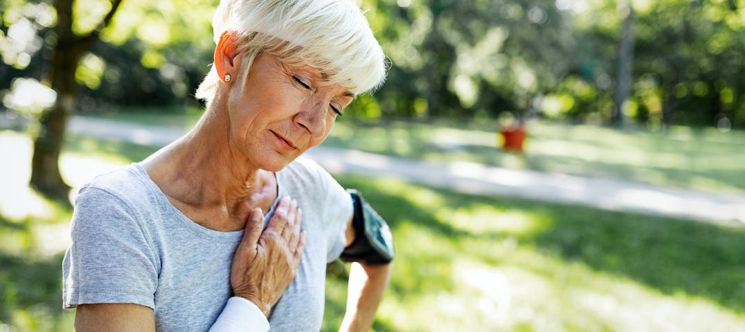 An older woman places her hand on her chest while working out.