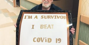 John Jones sits in a wheelchair and holds a sign celebrating his recovery from COVID-19.