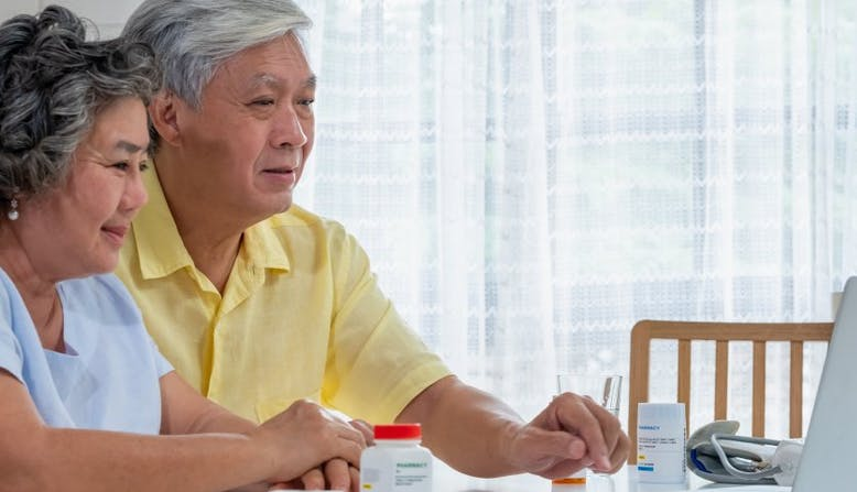 An older couple sits in front of a laptop and medication bottles.