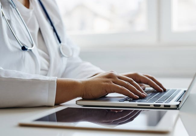 A doctor types on a laptop on a white desk.
