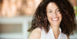 A lady with curly brown hair smiling outside.