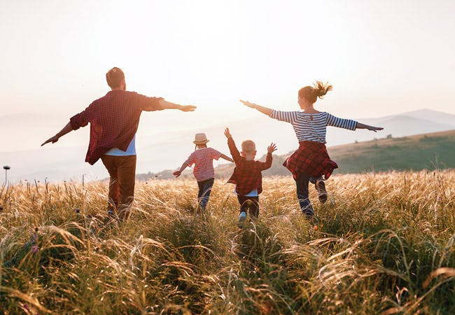 A family walk through a field together, with their arms out.