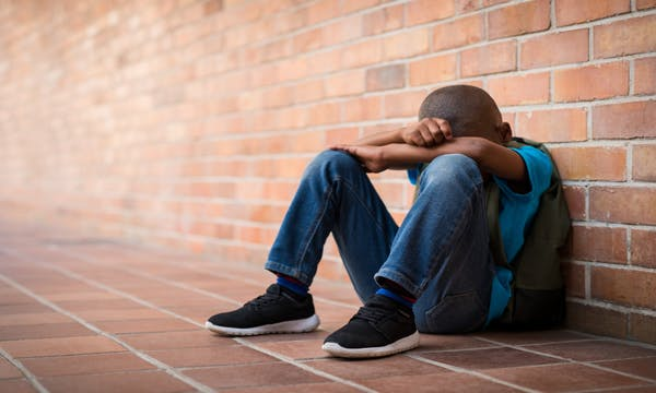 A boy sits outside of school after being bullied.