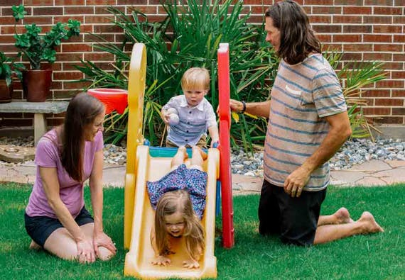 A family with two small children play outside on a playground.