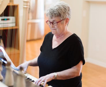 Carol Selby, NPF research ambassador, plays the piano and wears red glasses.