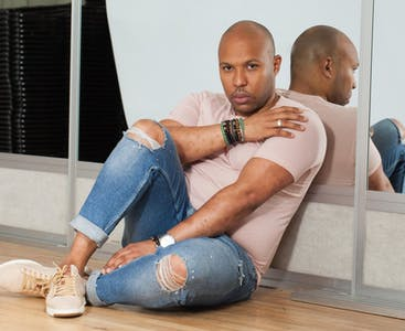 Edgar Payano sits on the floor of a dance studio, displaying his skin.