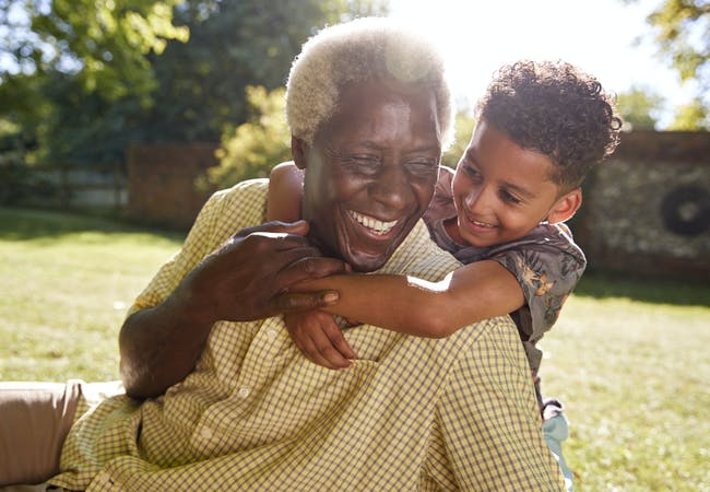 A smiling man sitting on grass, embraced by his grandson.