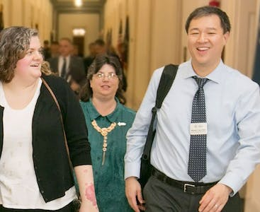 Wilson Liao and advocates walk together in a government building.