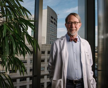 Philip Mease smiles in front of a large window while wearing a lab coat and bow tie.