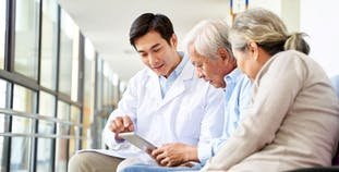 A doctor discusses treatment with a patient and his spouse.