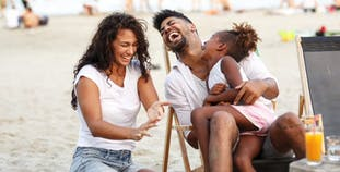 A family laughing together on the beach.