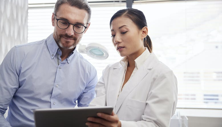 A female health care professional looking at an iPad with a male health care professional.