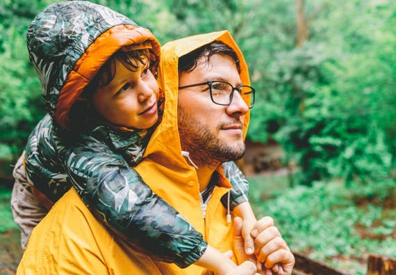 A father holds his son on his shoulders on a rainy day in the woods.