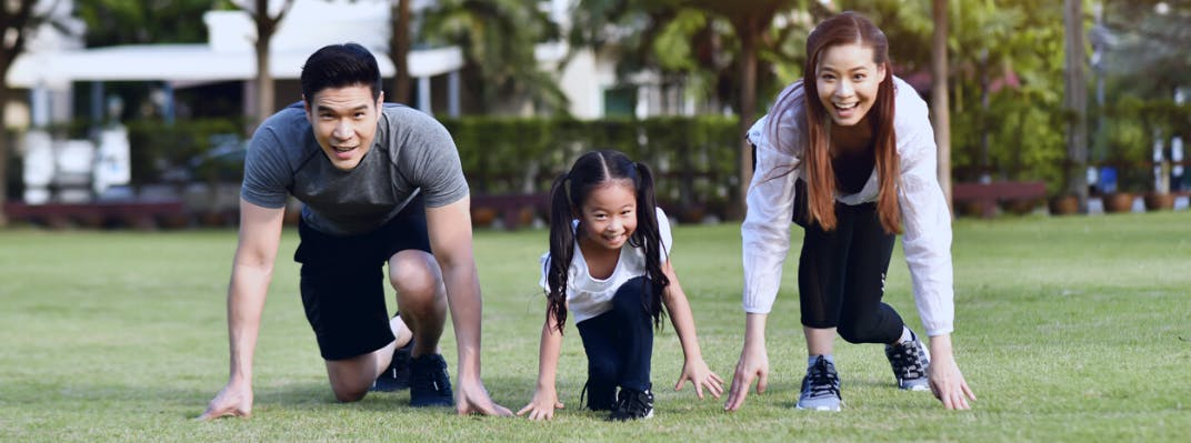A family crouches down preparing to race each other in a park.
