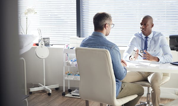A dermatologist discusses results with a patient in an exam room.