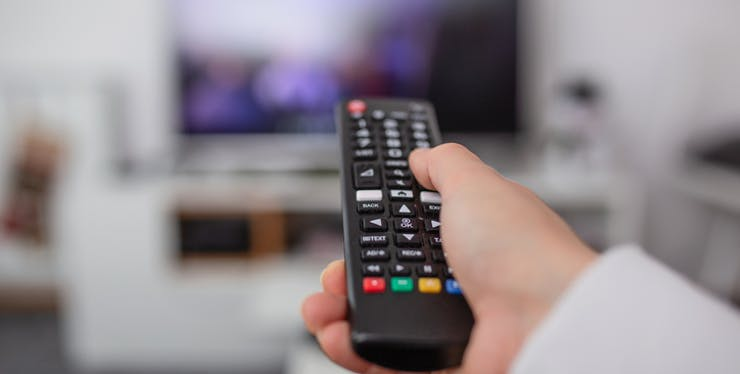 pessoa segurando um controle de televisão