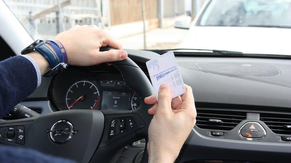 Conductor muestra su permiso B de conducir