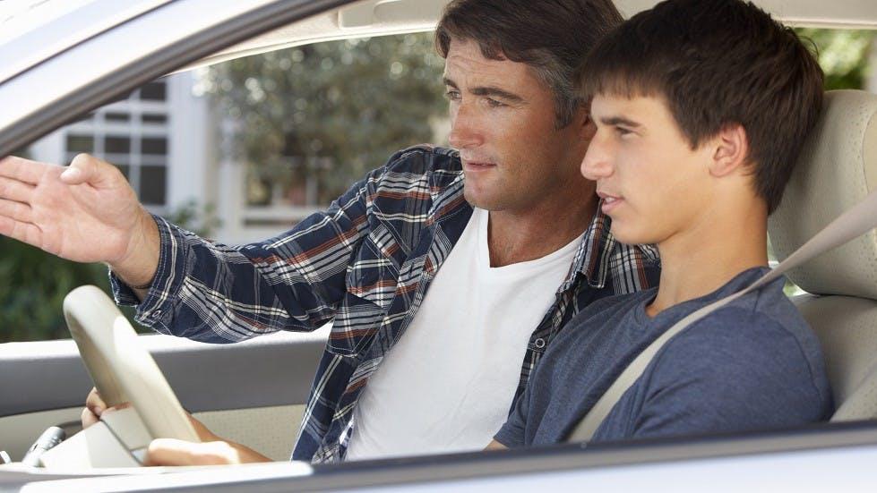 Padre enseñando a conducir a su hijo