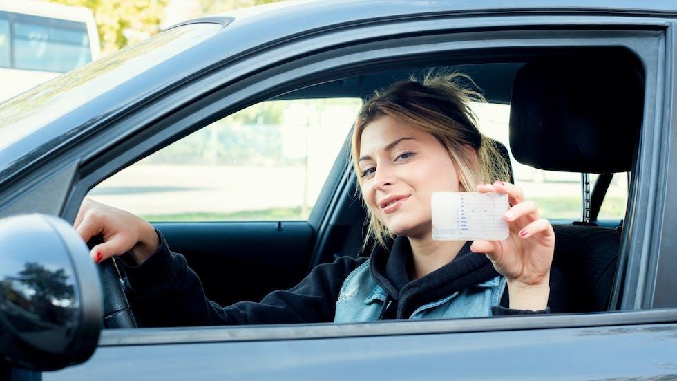 Conductora muestra su carnet de conducir.