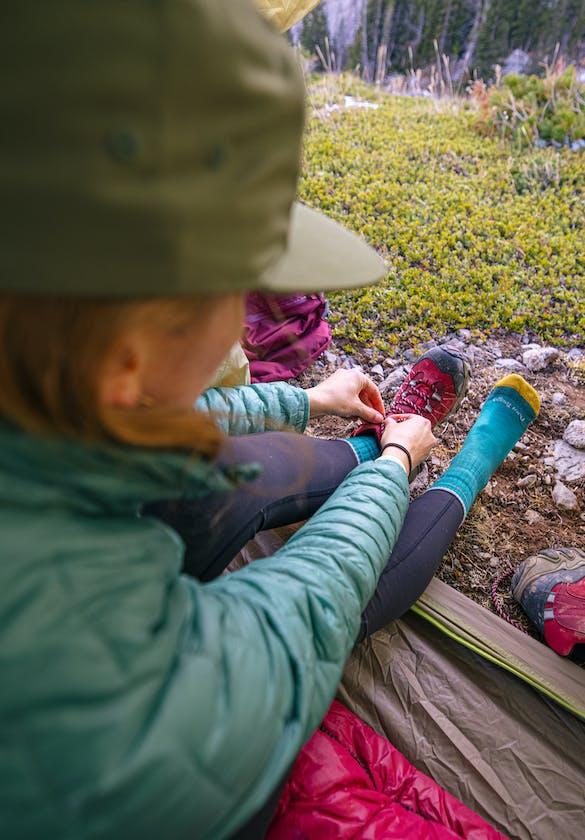 Camper taking unlacing her Women's Bridger Mid Waterproof
