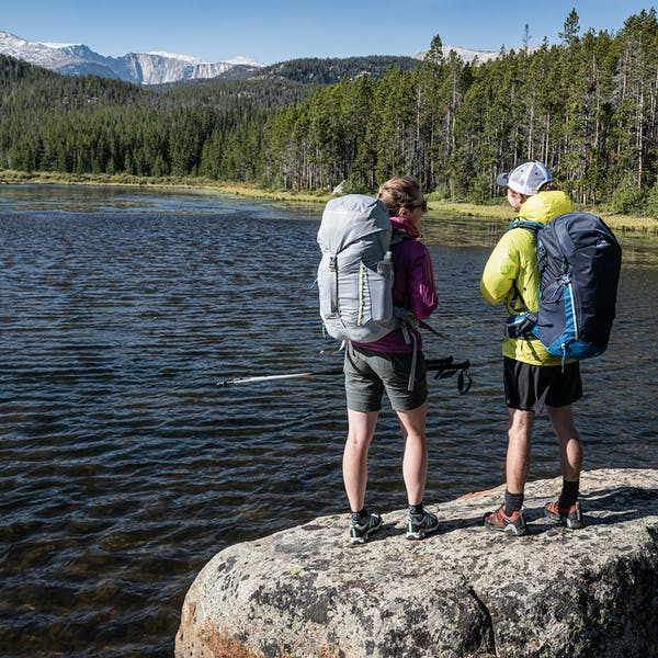 Hikers overlooking mtn lake wearing the Oboz Arete