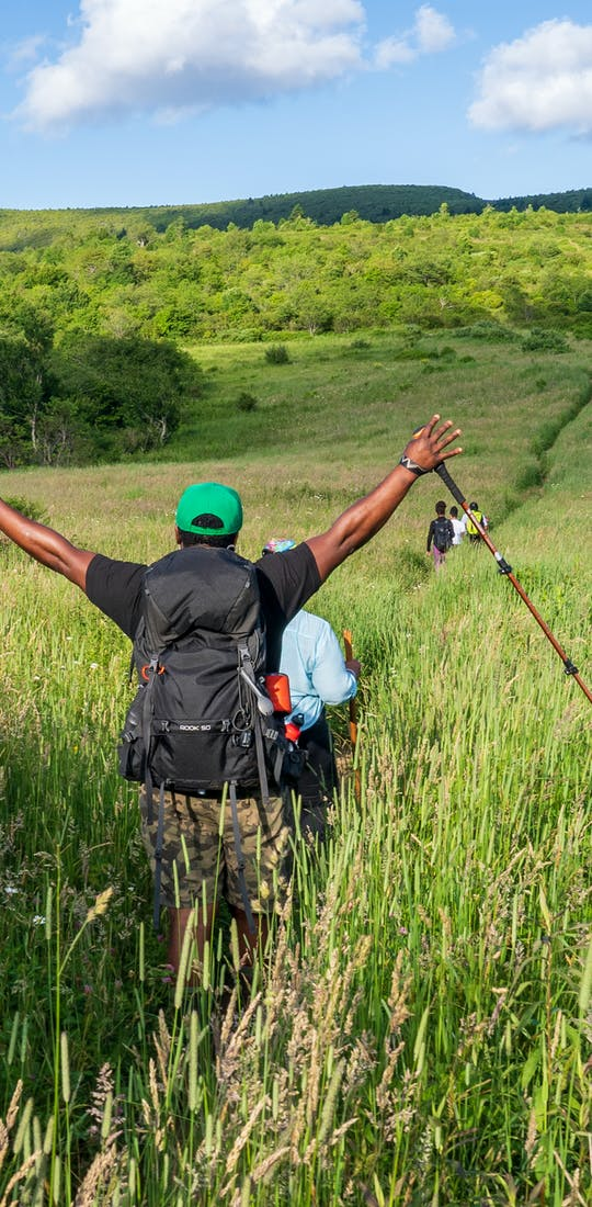 Hiker is raising hands victoriously while walking through a grassy plain