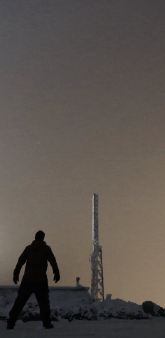 A person standing on the top of the Mt. Washington Observatory in winter at night.