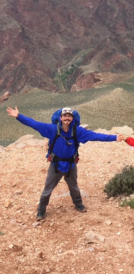 Two adventurers with arms wide open at the top of the mountain landscape.