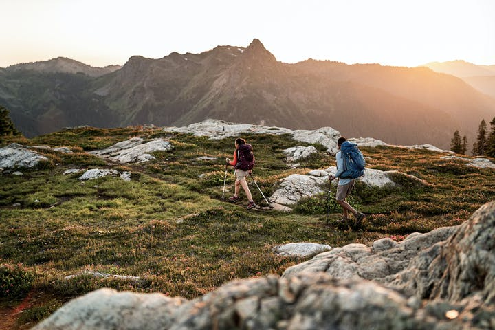 Two hikers on the trail overlooking mountain range