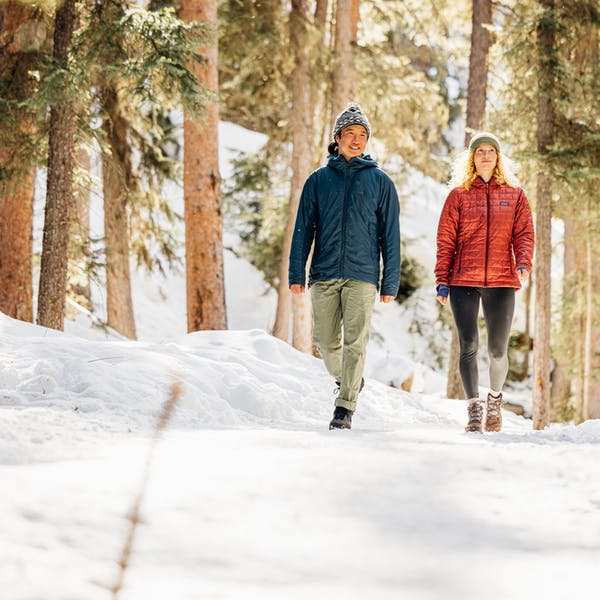 A couple waking on a snowy trail deep in the woods