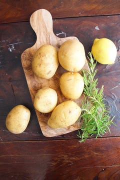 7 whole potatoes and springs on rosemary on a chopping board