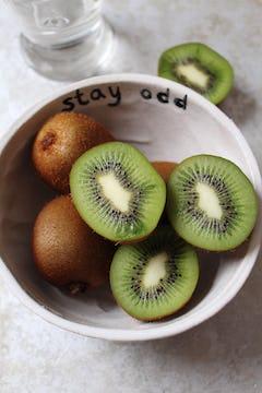 A bowl of kiwis. 3 kiwi halves are up facing the camera.