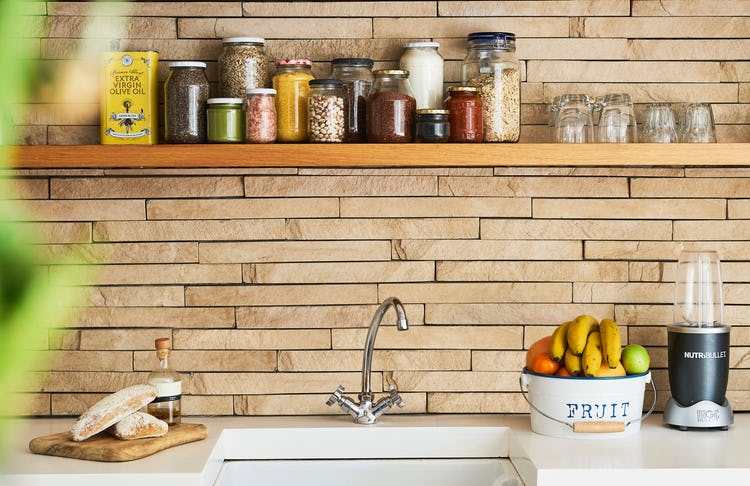 kitchen sink, on the right hand its a bucket of fresh fruit, nutribullet blender. On the left side wooden board with fresh baked bread and a bottle. Above glass jars of cooking supplies and drinking glass