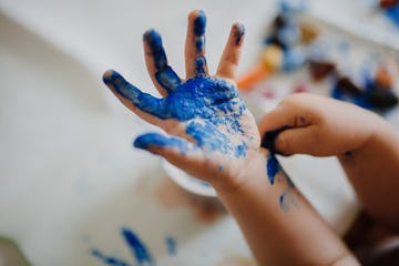 A child's hand covered in blue paint.