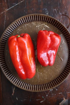 2 red bell peppers on a baking tray