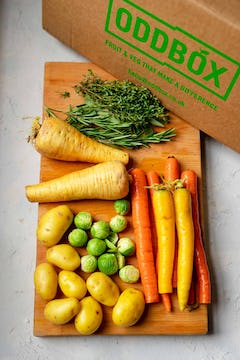 The contents of a Christmas Oddbox, with sage, rosemary, thyme, parsnips, carrots, potatoes, and brussel sprouts.