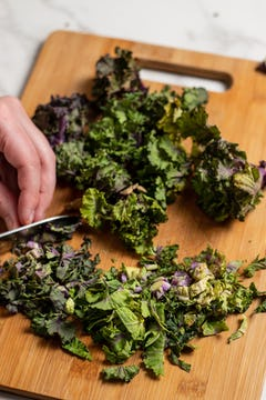 Bunch of fresh kalettes getting chopped on a wooden chopping board